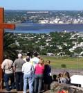Jovens fazem oração com a Cruz da JMJ no alto da Fortaleza do Cerro, com vista para toda Montevidéu e a baía do Rio da Prata.