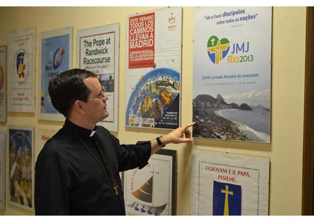 Padre João Chagas diante dos cartazes das JMJ's na sede do PCL em Roma